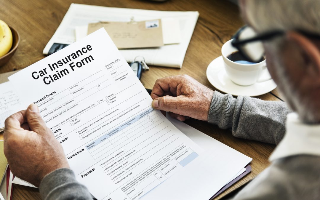Elderly man filling out car insurance claim form