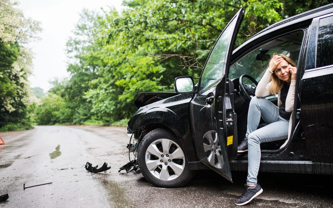 Young frustrated woman sitting in the damaged car after a car accident, making a phone call.