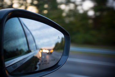 side-view mirror of car with traffic in the reflection